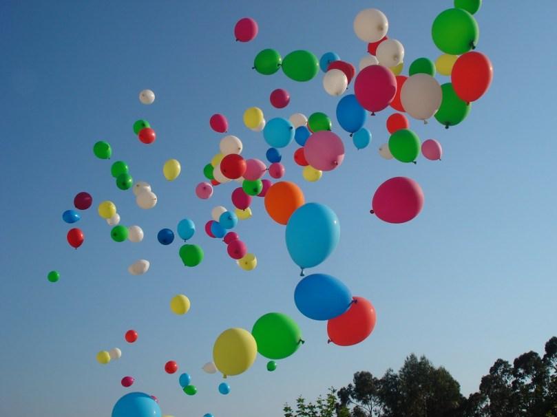 Foto tirada de baixo para cima, de inúmeros balões coloridos voando em direção ao céu.