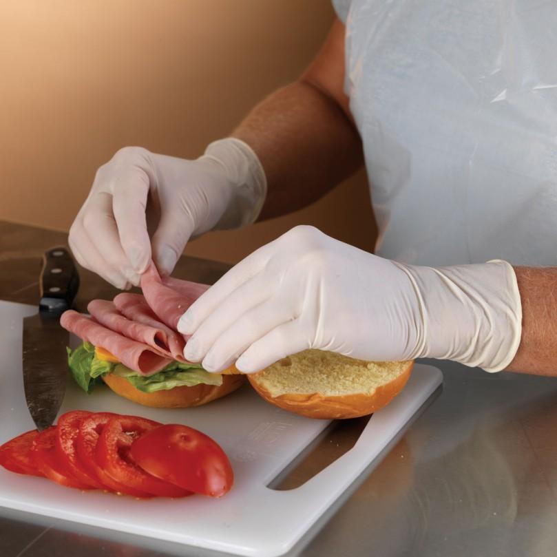Foto em que aparecem mãos vestidas com luvas de látex preparando um sanduíche, com fatias de tomate e presunto cortadas sobre uma tábua de plástico.