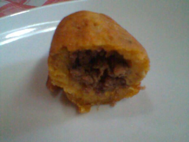 Foto de um bolinho partido ao meio mostrando o recheio com a carne moída, sobre um prato branco.