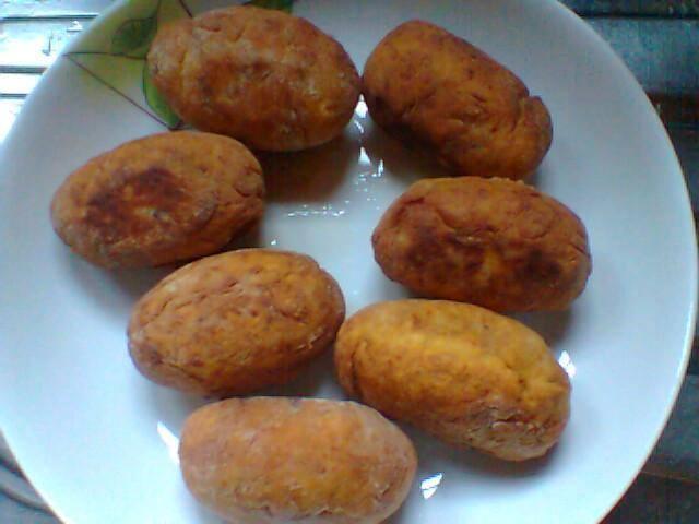 Foto dos bolinhos já fritos e servidos sobre um prato branco.