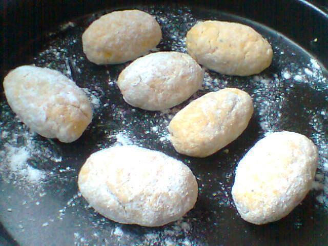 Foto dos bolinhos já em suas formas, colocados em uma fôrma preta e polvilhados com farinha branca.