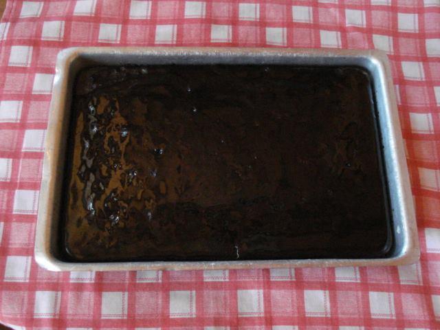 Foto de um bolo Nega-Maluca, já pronto, dentro de uma forma de metal, que está sobre uma mesa com uma toalha quadriculada com as cores vermelho e branco.