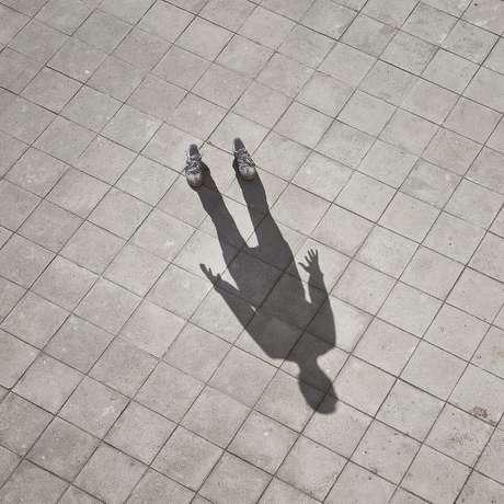 Foto da sombra de um homem projetada na calçada. O homem que projeta a sombra não aparece na imagem, somente seus tênis.