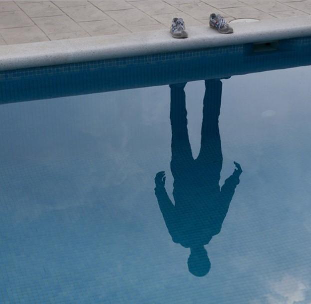 Foto da sombra de um homem projetada em um espelho d'água. O homem que projeta a sombra não aparece na imagem, somente seus tênis.