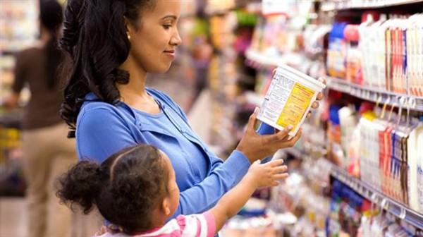 Imagem de uma mãe lendo o rótulo da embalagem de um produto na frente de uma prateleira de um supermercado, enquanto sua filha tenta alcançar o produto com sua mão direita.