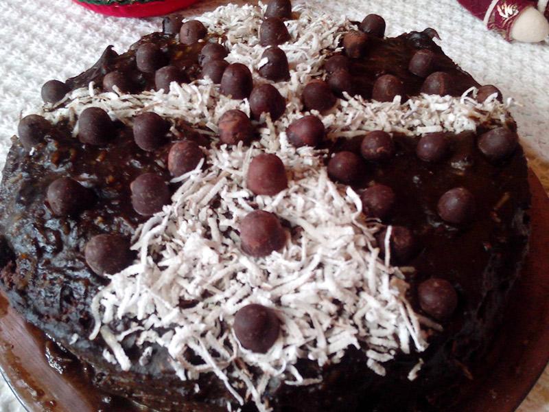 Foto da Torta Daisy já montada, com cobertura de brigadeiro SLA, gotas de chocolate e coco, sobre um prato de vidro.
