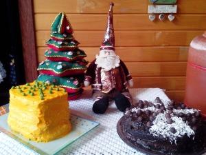 Foto de uma mesa decorada com um pinheirinho de natal feito de almofadas de pano, um papai noel e dois pratos com receitas de natal, onde uma delas é a Torta Daisy.